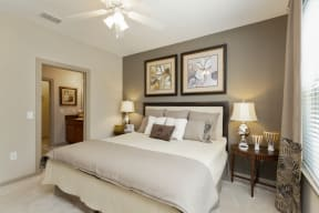 The Grove at Waterford Crossing Apartments in Hendersonville - Bedroom with Stylish Decor, Wall to Wall Carpet, Green and White and Grey Walls, Ceiling Fan, and Access to Bathroom