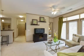 Hendersonville Apartments for Rent -The Grove at Waterford Crossing Living Room with Stylish Decor, Wall to Wall Carpet, Ceiling Fan, Window, and Access to Dining Area and Hallway