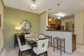 The Grove at Waterford Crossing Kitchen with Black/Stainless Steel Appliances, Wood Cabinets, and Access to Dining Room