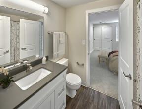 Ensuite bathroom with hard wood style flooring, toilet and vanity sink.