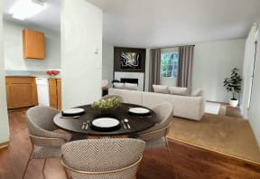 Open layout dining room between kitchen and living room. Contains round dining table and 4 chairs. Living room in background contains large sofa, window and corner fireplace.