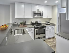 Updated kitchen with stainless steel appliances, white cabinets, and grey countertops.