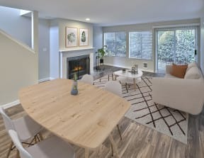 Living and Dining open layout with a fireplace, lots of windows and finished with a small dining set, coffee table and couch.