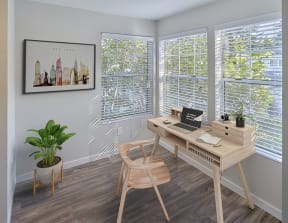 Room stage with office furniture. Three large windows let in a lot of natural light. Area has hard wood style flooring.