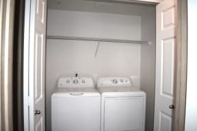 A washer and dryer side by side with a shelf above in a closet with accordion doors.