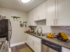 Apartments for Rent in Temecula - Vista Promenade Kitchen with White Cabinetry, Stainless Appliances, Quartz Countertops, Harwood Flooring, and Beige Walls
