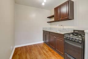 Apartments for Rent in Colton, CA - Las Brisas Kitchen with Stainless Appliances, White Cabinets, Plank Flooring, and Granite Countertops