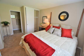 The Arches at Regional Center West Apartments in Antelope Valley - Bedroom with Stylish Decor, Wall to Wall Carpet, White Walls, Sliding Door Closet, and Access to Bathroom