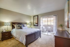 Vista Promenade Apartments in Temecula - Bedroom with Stylish Decor, Wall to Wall Carpet, Beige Walls, and Access to Patio/Balcony
