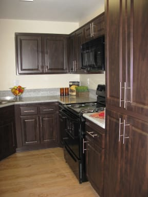 Apartments for Rent in Antelope Valley, CA - The Arches at Regional Center West Kitchen with Black Appliances, Granite Countertops, Plank Flooring, and Dark Mocha Cabinets
