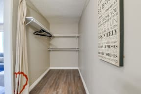 Colton, CA Apartments - Las Brisas Walk-In Closet with Shelves and Hangers, Beige Walls, and Plank Flooring