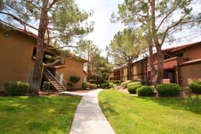 Antelope Valley, CA Apartments - Walkway with Exterior View of The Arches at Regional Center West Apartment Buildings Surrounded by Lush Landscaping