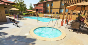 The Arches at Regional Center West Apartments in Antelope Valley, CA - Sparkling Swimming Pool and Spa Surrounded by Lounge Chairs with Covered Tables