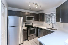 Renovated kitchen with dark cabinets, light counters