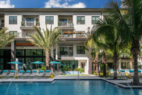 Pool deck with lounge chairs and umbrellas  | District at Rosemary