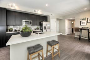 kitchen with white quartz countertops and dark wood cabinets