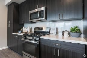 kitchen with dark wood cabinets, white quartz countertops and stainless and black appliances