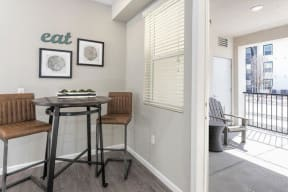 Dining nook with high top table and two stools | area opens to patio