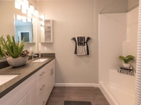 bathroom with white cabinets and shower-tub combination
