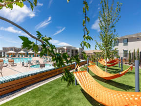 lawn with hammocks poolside at Lumina apartments