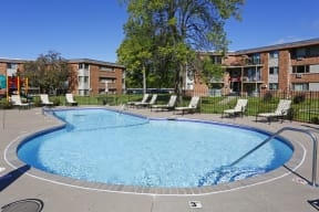 Outdoor pool with black fencing and plenty of lounge chair seating.