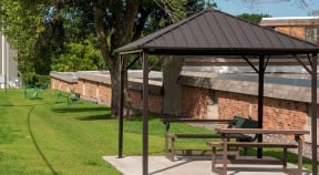 Shaded gazebo in the grass perfect for an outdoor picnic or get together.