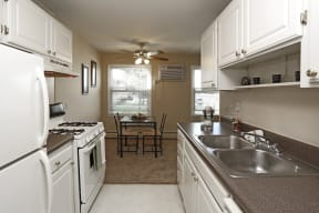 White cabinetry kitchen leads into the separate dining area.