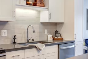 Bright kitchen with white cabinetry and Cesar Stone Quartz countertops.
