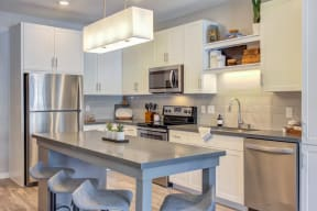 Modern kitchen with bright white cabinetry, stainless steel appliances, and custom kitchen islands.