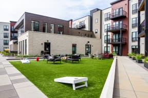 Large green space outlined by sidewalks with plenty of outdoor game options like cornhole.