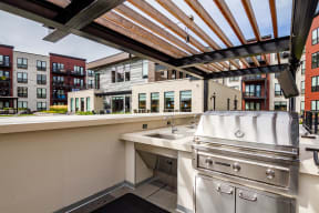 Outdoor grilling station with counterspace and a sink all shaded by an overhead pergola.