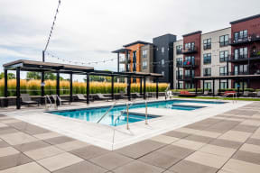 Outdoor pool at Ironwood complete with gazebos, lounge seating, and lights hanging above the deck.