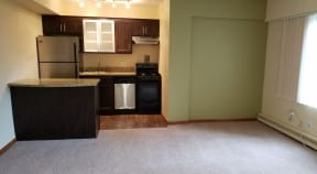Unfurnished carpeted living room connected to small kitchen