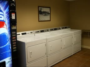 Four washers and dryers side by side next to vending machine