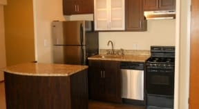 Kitchen with dark wood cabinets, granite countertops and stainless steel appliances