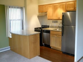 Kitchen with light wood cabinets, half breakfast bar and stainless steel appliances