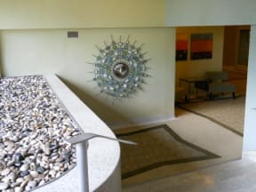 Lobby stairs next to bed of rocks and decorative art
