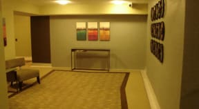 Lobby with large carpet, chair, and wall art