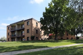 Exterior of Wingate Apartments surrounded by lush grass and large trees.