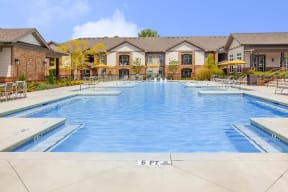 Well-maintained swimming pool and lounging chairs with parasols in One White Oak apartment rentals