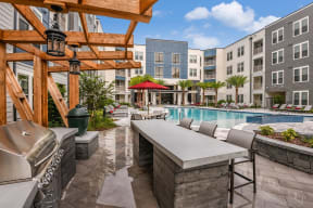 Modern BBQ grill with seating by resort-style swimming pool in Orlando, FL apartments for rent