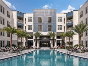 Well-maintained swimming pool and lounging chairs with parasols in Coda Orlando apartment rentals