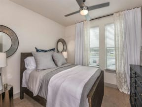 Model bedroom with carpeted flooring and two window in Orlando, FL apartment for rent