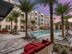 Spectacular Coda Orlando swimming pool with lounging chairs and tall palm trees in Orlando, FL