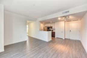 Living Room with Hardwood Inspired Floor, View of Kitchen, and Door