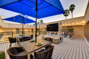 Outdoor patio with TV, Tables, Chairs and Blue Umbrella