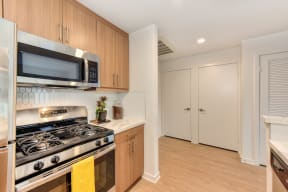 Kitchen with Gas Stove, Refrigerator and Wood Cabinets