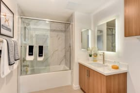 Bathroom with Marble inspired Tub Enclosure, Wood Cabinets, and Mirror