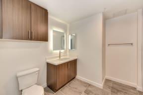 Bathroom with Hardwood Inspired Floor, Toilet, Wood Cabinets, and Sink