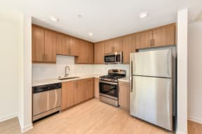 Kitchen area with Hardwood Inspired Floor, Refrigerator, Stove, Oven and Dishwasher
